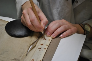 Using a mounted needle to remove rust from the parchment where ferrous needles were previously in place.