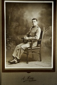 Mounted, sepia-tinted photograph portrait of Elphick seated in uniform with a corporal's stripes. Photographed by A. Hing of Hong Kong